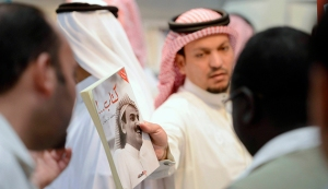 A man shows a book by Saudi writer and poet Al-Rotayyan during the Riyadh Book Fair in Riyadh