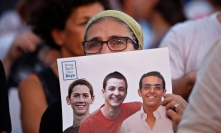 An Israeli woman holds a sign with the images of the three missing Israeli teenagers in Tel vai